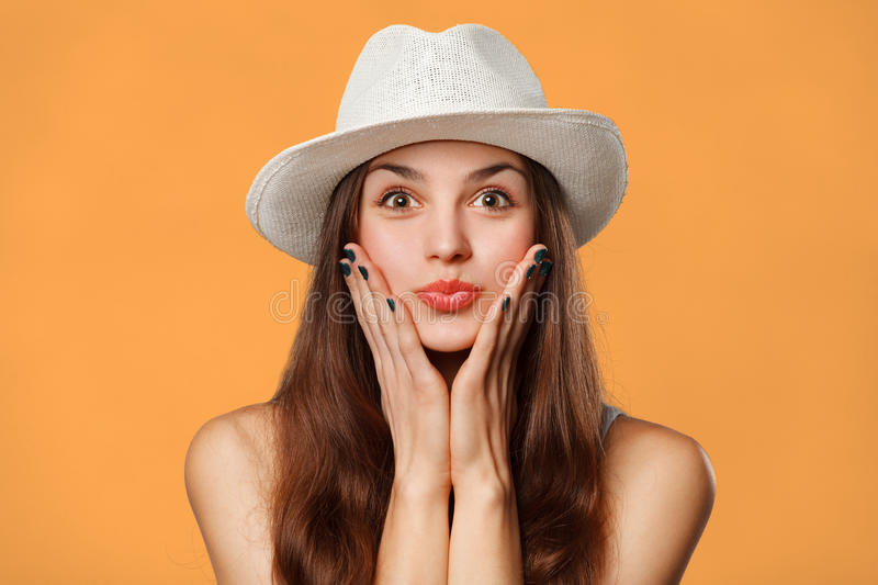 Surprised happy beautiful woman looking sideways in excitement. Excited girl in hat, isolated on orange background stock photography