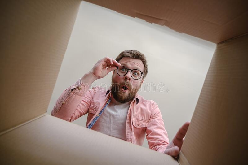 Surprised man looks into the unpacked delivered box with the order, hold glasses with hands and rejoices. Unboxing. Surprised, happy man looks into the unpacked stock photography