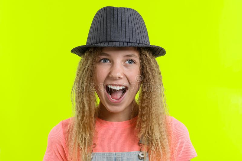 Surprised happy teen girl with curly hair in hat looking at the camera with open mouth over yellow studio background royalty free stock images
