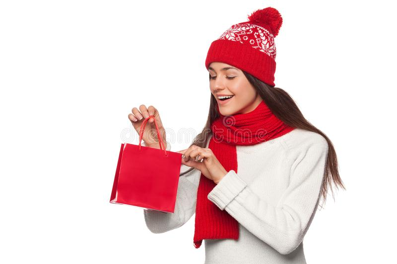 Surprised happy woman holding and looks in red bag in excitement, shopping. Christmas girl on winter sale with gift, isolated stock photos