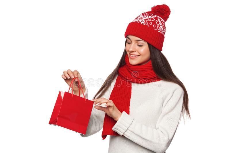Surprised happy woman holding and looks in red bag in excitement, shopping. Christmas girl on winter sale with gift, isolated royalty free stock images