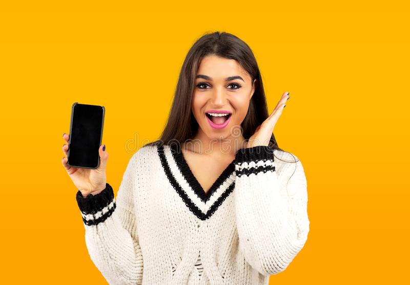 Surprised happy woman in white sweater showing a new smartphone royalty free stock images
