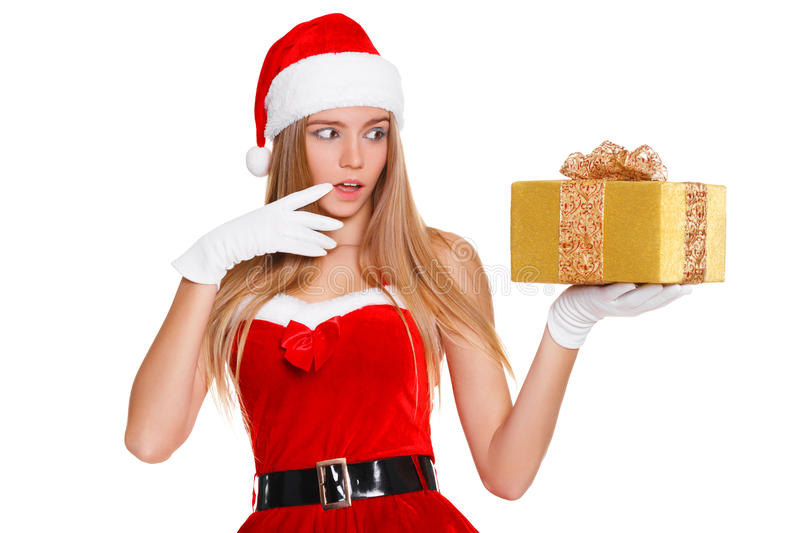 Surprised happy young woman in santa claus clothes looking on christmas gift in excitement. Isolated over white background royalty free stock photography