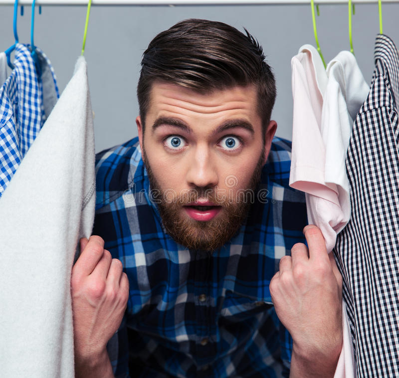 Surprised hipster man standind near rack with clothes royalty free stock image