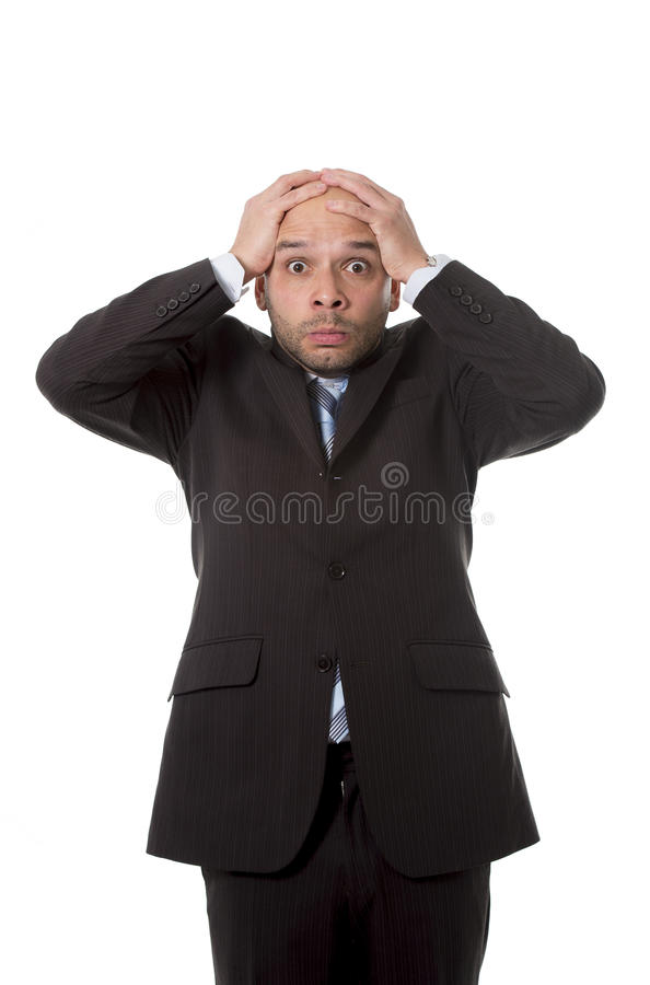 Surprised Hispanic businessman in stress and shock wearing suit and tie looking scared, clueless and confused stock photography