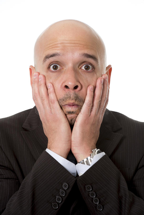 Surprised Hispanic businessman in suit and tie looking scared, shocked and confused with hands on his face stock image