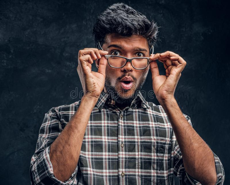 Surprised Indian guy lowers his glasses and looks at the camera. Studio photo against a dark textured wall royalty free stock photography