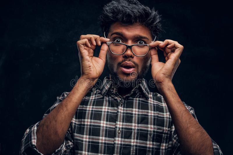 Surprised Indian guy lowers his glasses and looks at the camera. Studio photo against a dark textured wall stock image