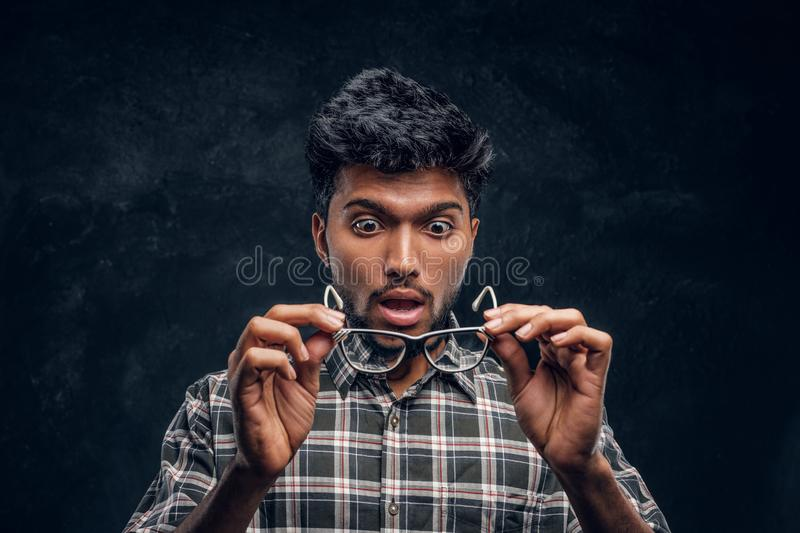 Surprised Indian guy lowers his glasses and realizes that now he can see without glasses. Studio photo against a dark textured wall stock photos