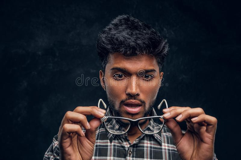 Surprised Indian guy lowers his glasses and realizes that now he can see without glasses. Studio photo against a dark textured wall stock images