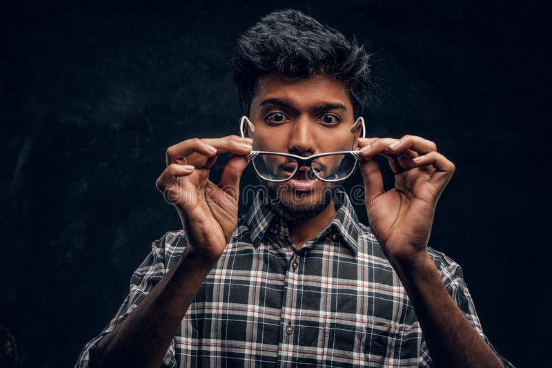 Surprised Indian guy lowers his glasses and realizes that now he can see without glasses. Studio photo against a dark textured wall royalty free stock photo