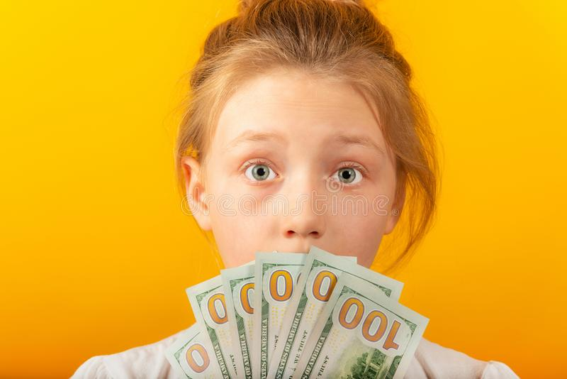 Surprised and joyful girl holds dollars in their hands and covers their face.  stock photos