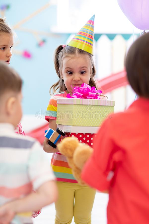 Surprised kid taking from friends gifting boxes indoors. Funny child weared birthday cap with presents. Surprised kid girl taking from friends gifting boxes royalty free stock photo