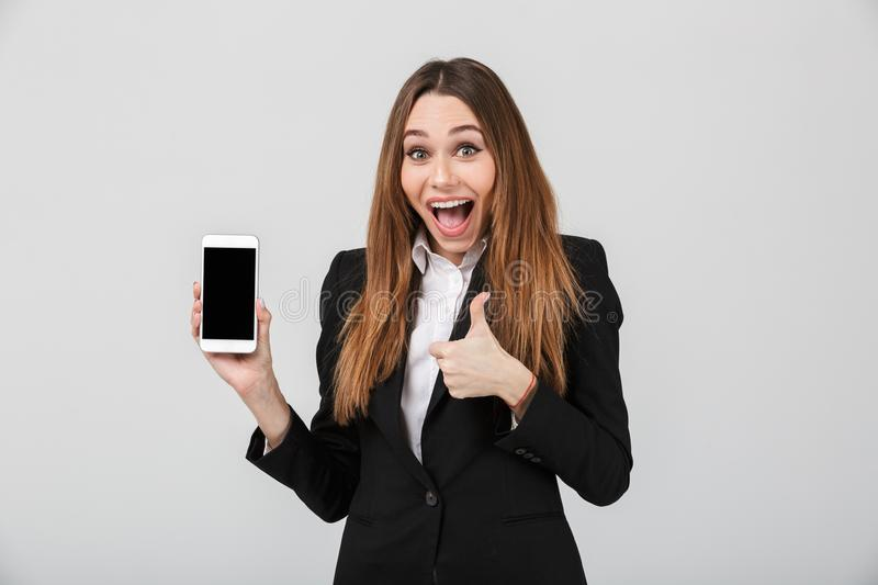 Surprised lady showing thumb up gesture and smartphone isolated stock photo