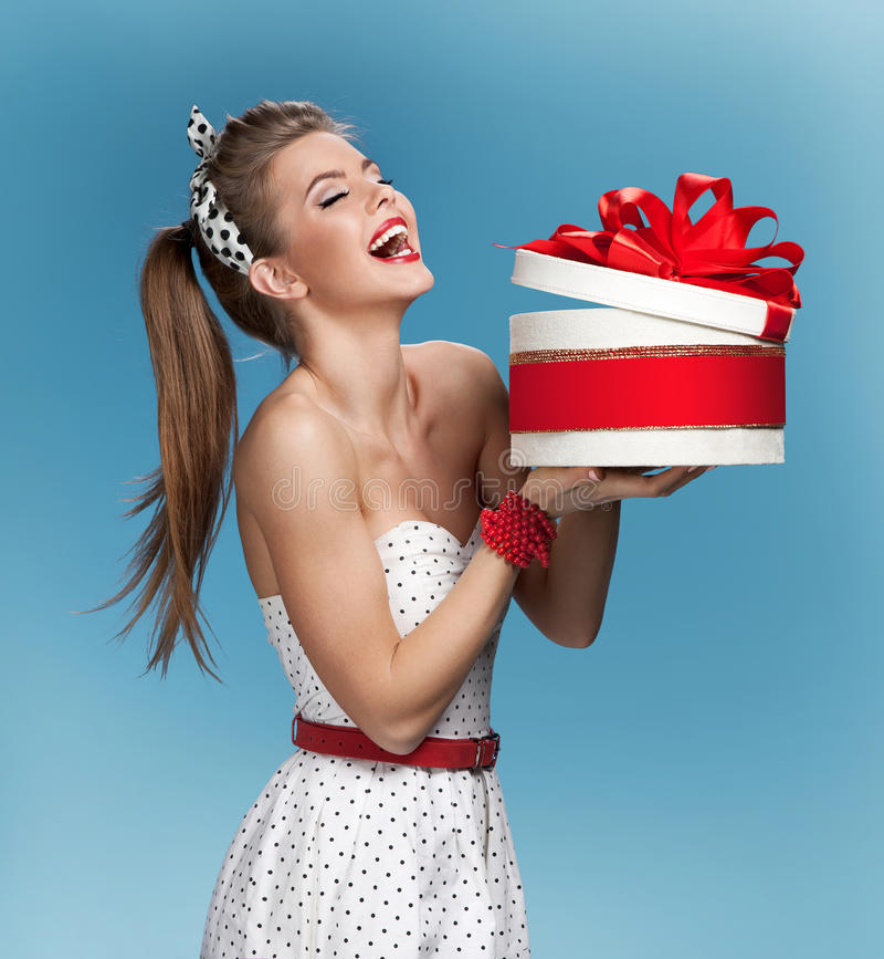 Surprised laughing beautiful young woman holding an open gift box over blue background. Holidays, holiday, celebration, birthday royalty free stock photos