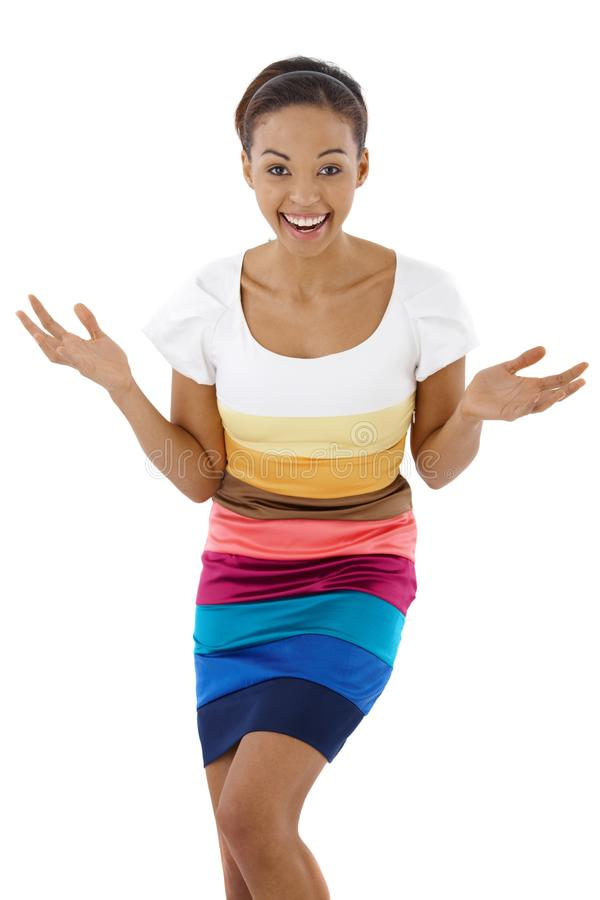 Surprised laughing ethnic girl. In multicolour dress, looking at camera stock photo