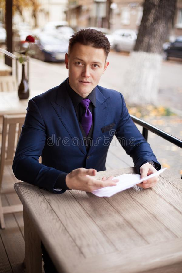 Surprised lawyer in a suit, looking through papers in a cafe stock images