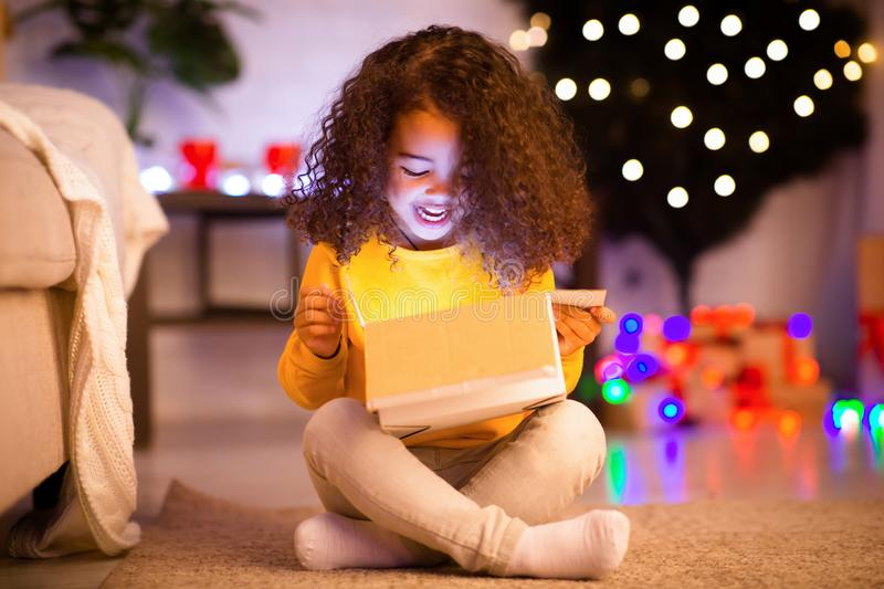 Surprised little african girl opening glowing Christmas gift stock image