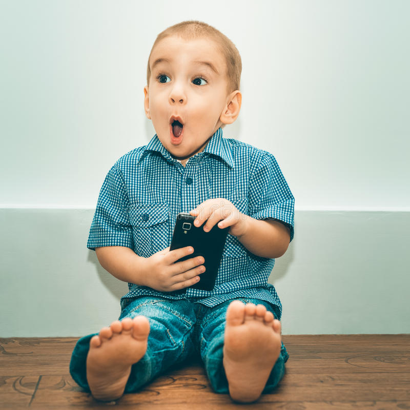 Surprised little boy with a cell phone. stock image