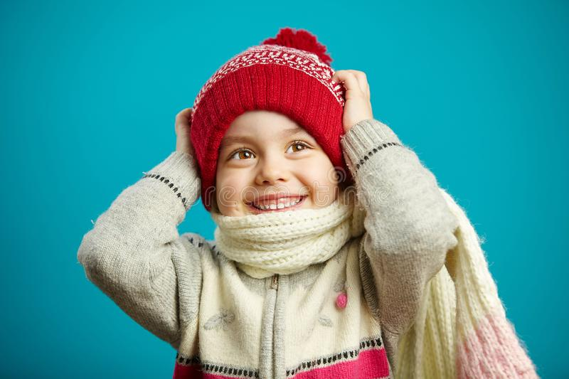 Surprised little girl in the christmas hat grabbed her head, expresses surprise and amazement, stands on blue background royalty free stock photography