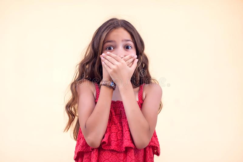 Surprised little girl closed her mouth with hands. Children and emotions concept royalty free stock image