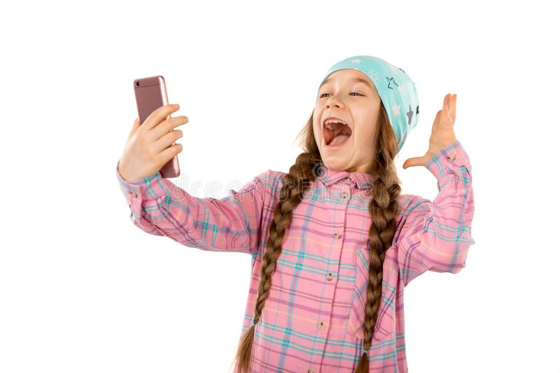 Surprised little girl holding mobile phone on white background. Games, children, technology concept stock image