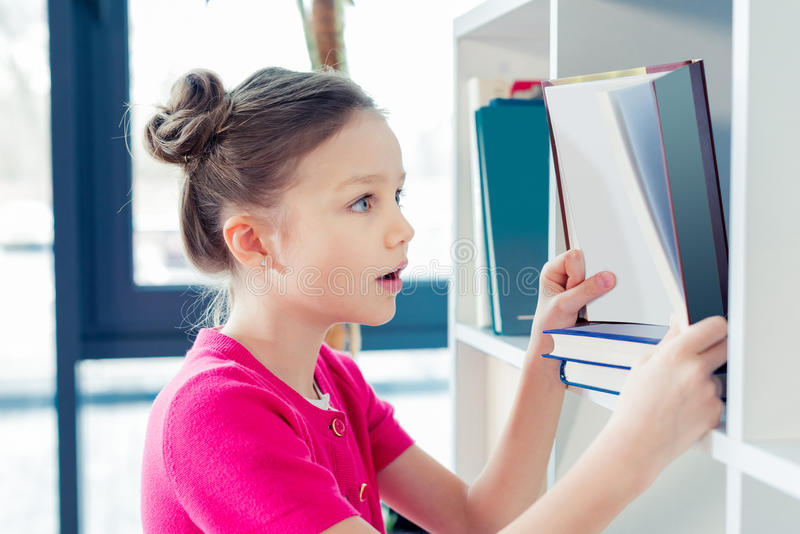 Surprised little girl holding open book and looking inside stock photo