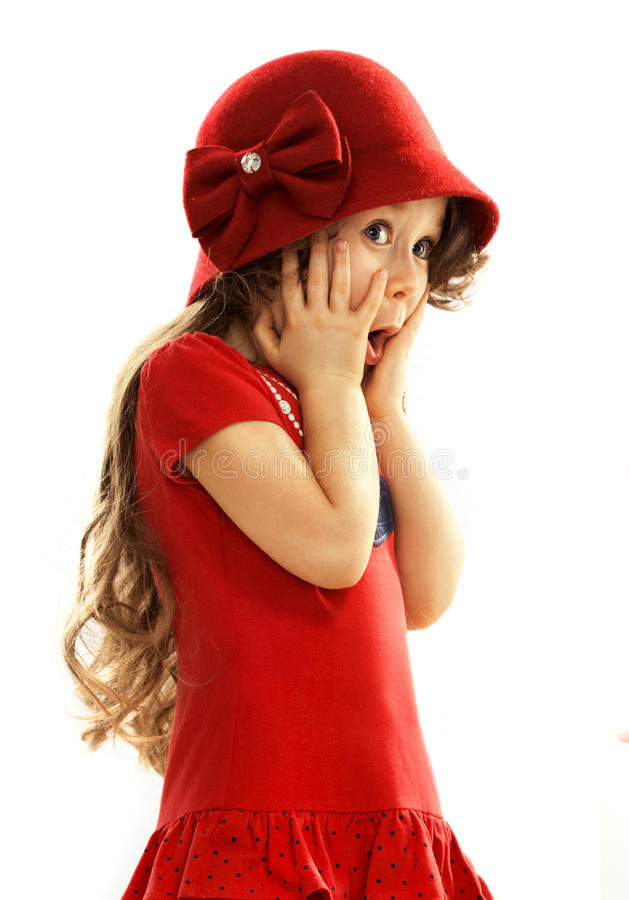 Surprised little girl in red dress. Little girl kid surprised with hands on her head isolated white background royalty free stock image