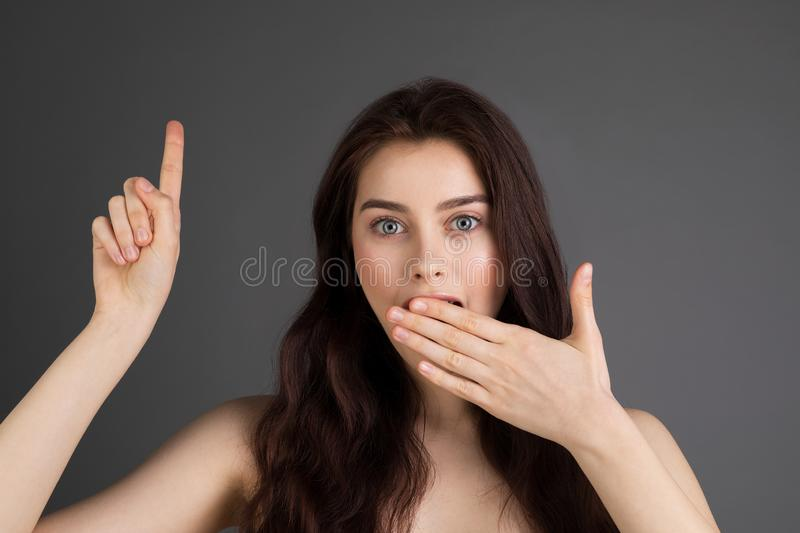 Surprised long haired brunette woman with blue eyes royalty free stock images
