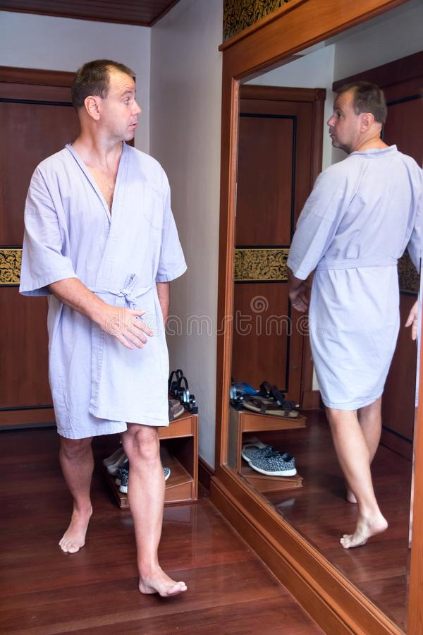 Reflection of man in the mirror is walking back. The surprised man in a bathrobe looking in the mirror at himself reflection. Reflection of man in the mirror is royalty free stock photography