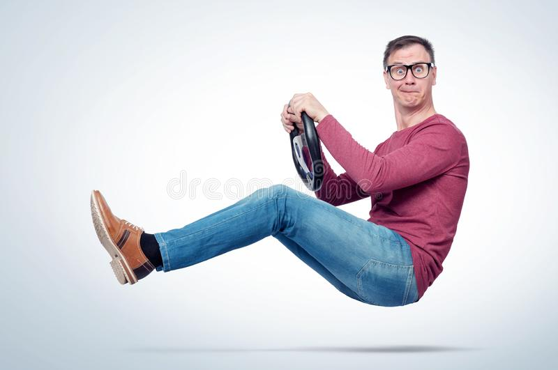 Surprised man in casual wear and glasses drives a car with a steering wheel. Auto driver concept.  royalty free stock photography
