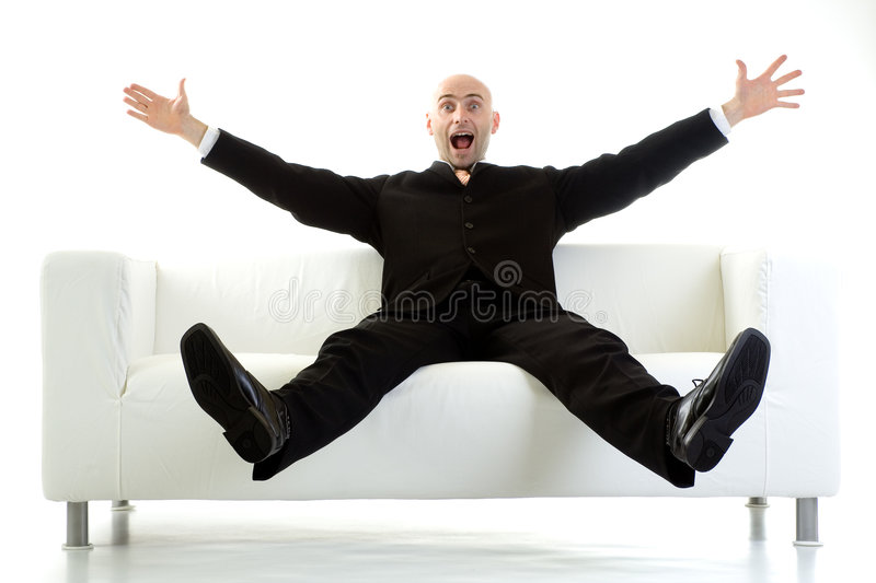 Surprised Man On Couch. Man in a black suit sitting on a white couch, with his arms and legs stretched out in the air and a look of surprise on his face stock photography