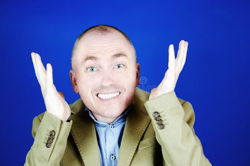 Surprised man in a cream coat throws up his hands to the sides on a blue background. Blank place for your advertisement. Surprised man in a cream coat throws up stock photography