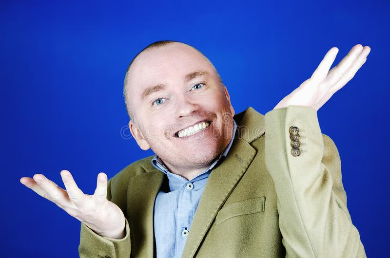 Surprised man in a cream coat throws up his hands to the sides on a blue background. Blank place for your advertisement. Surprised man in a cream coat throws up royalty free stock photography