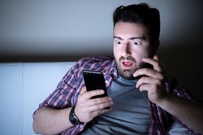 Surprised man expression using phone at night. Happy man texting on mobile phone at night stock images