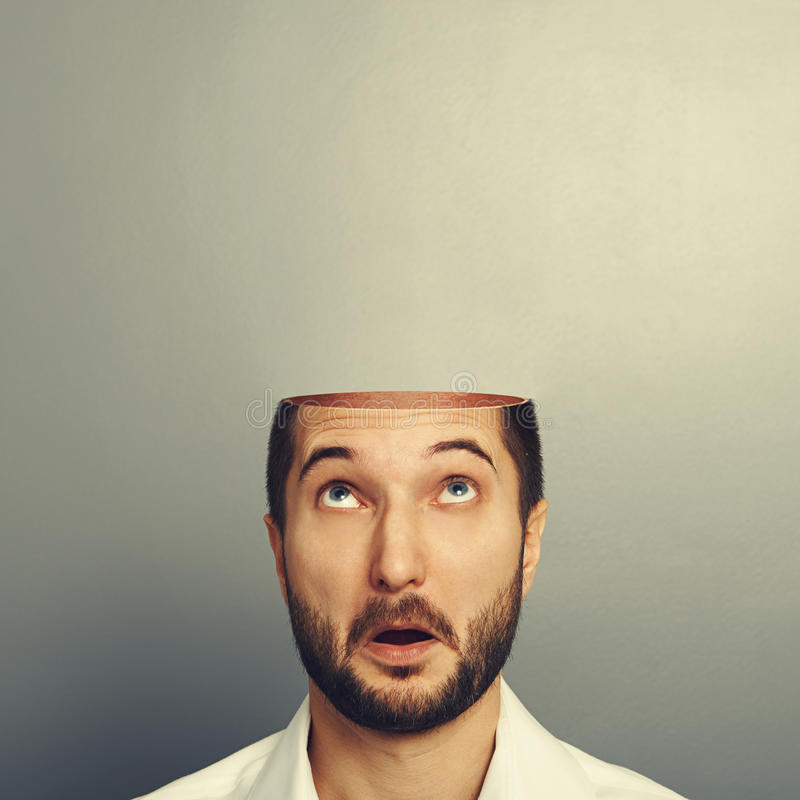 Surprised man looking up at his open empty head stock photos