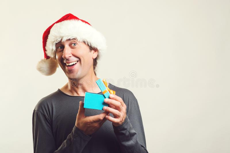 Surprised man opening Christmas gift over white. Handsome man in Santa hat with present, enjoying Christmas. Copy space. Christmas stock photos