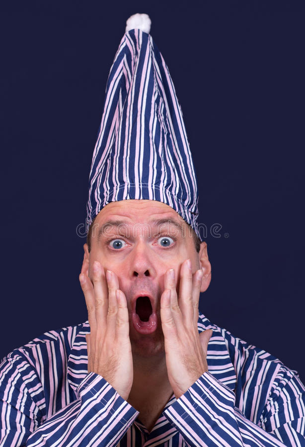 Surprised man in pajamas. Surprised man with a sleeping cap royalty free stock photos