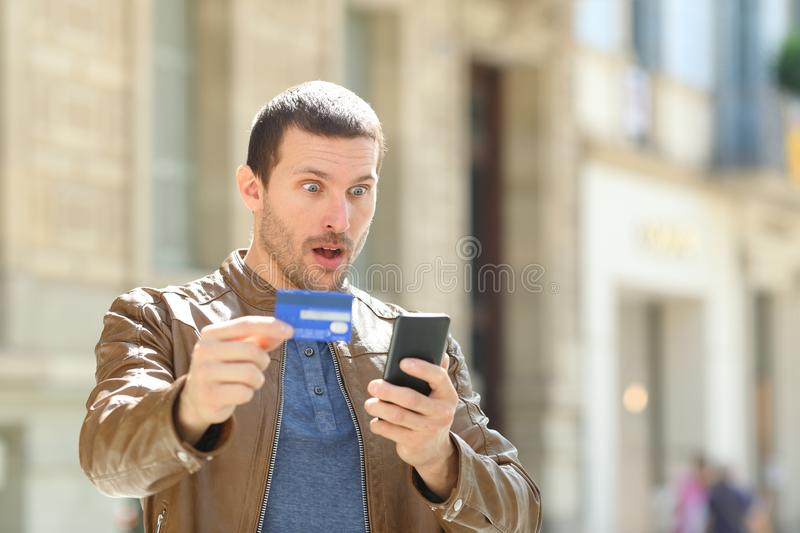 Surprised man paying with credit card and phone. Surprised man paying on line with credit card and mobile phone in the street royalty free stock photo