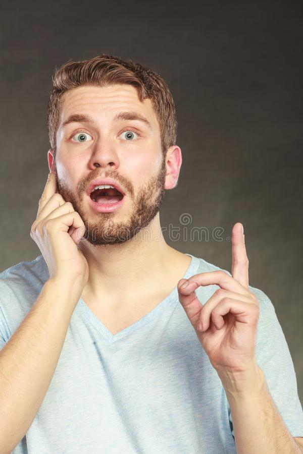 Surprised man pointing at empty blank copy space. Portrait of surprised scared handsome man pointing at empty blank copy space. Young guy in studio on black royalty free stock image