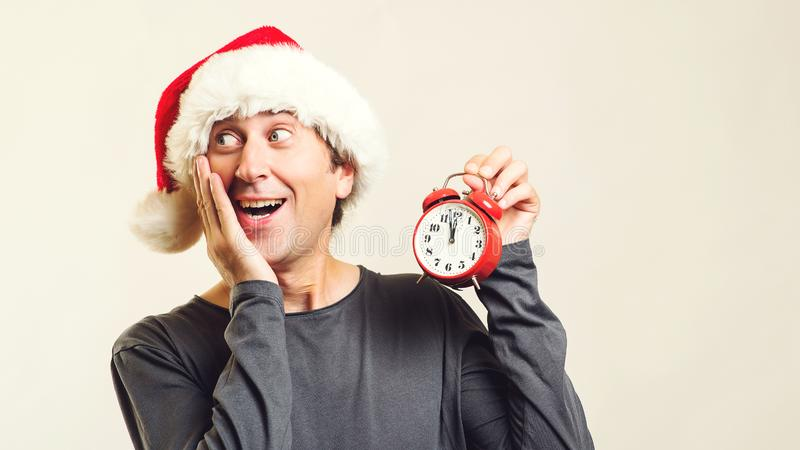 Surprised man in Santa helper hat with clock. Last minute christmas shopping. Time is coming. New Year and Christmas. Christmas royalty free stock image
