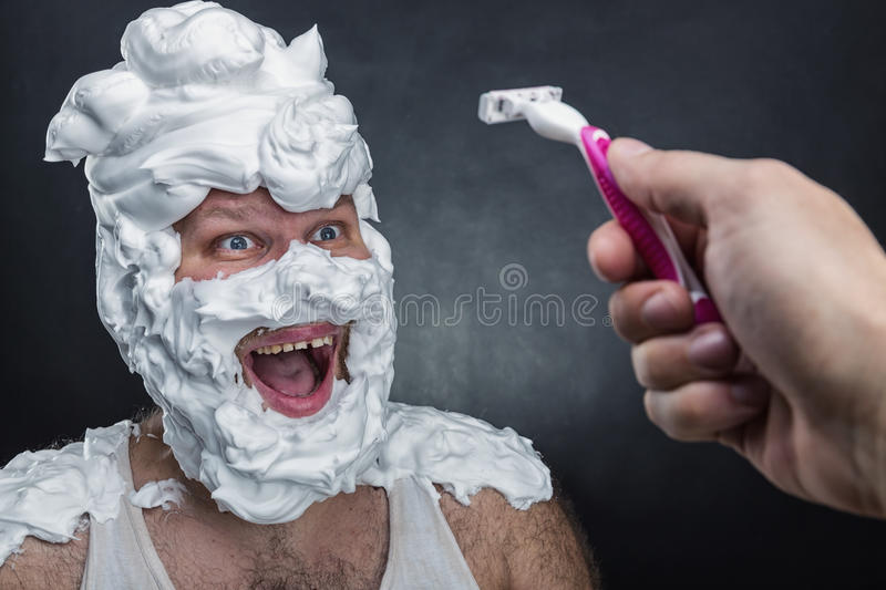 Surprised man with shaving foam on his face. Over grey background stock photo