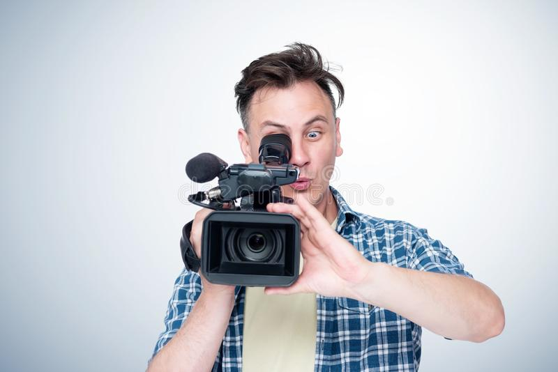 Surprised man shoots a video with a professional camcorder, front view. royalty free stock image