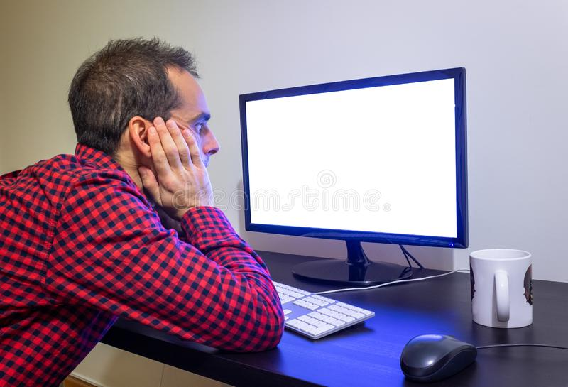 Surprised Man Stares at Office Computer on Wooden Black Desk Mockup. Dotted Red Shirt, LCD Screen, Keyboard, Mouse, White Mug. Copy Space stock photos