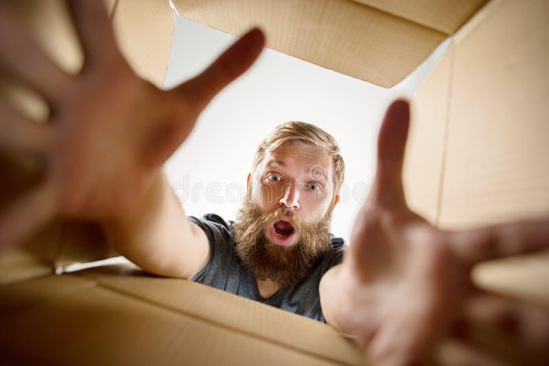 Man unpacking and opening carton box and looking inside. The surprised man unpacking, opening carton box and looking inside. The package, delivery, surprise stock photo
