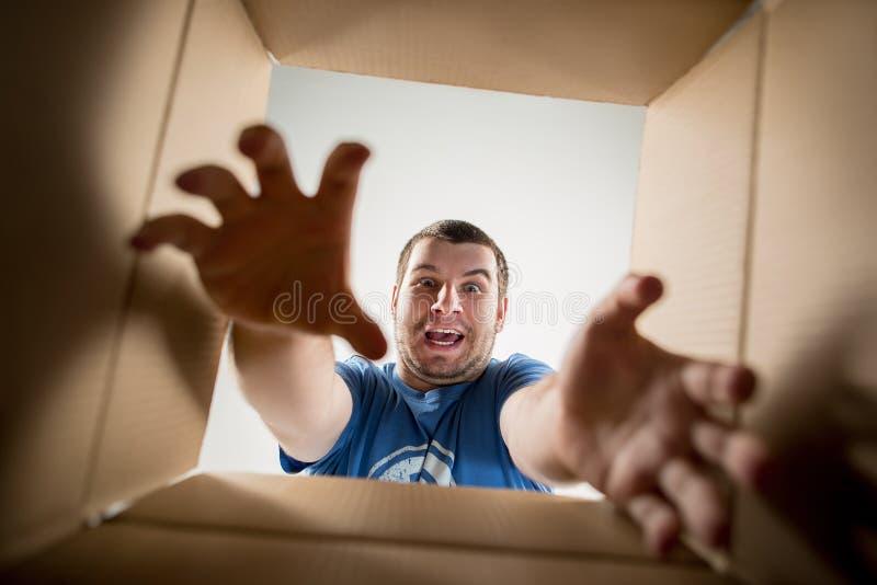 Man unpacking and opening carton box and looking inside. The surprised man unpacking, opening carton box and looking inside. The package, delivery, surprise royalty free stock photo