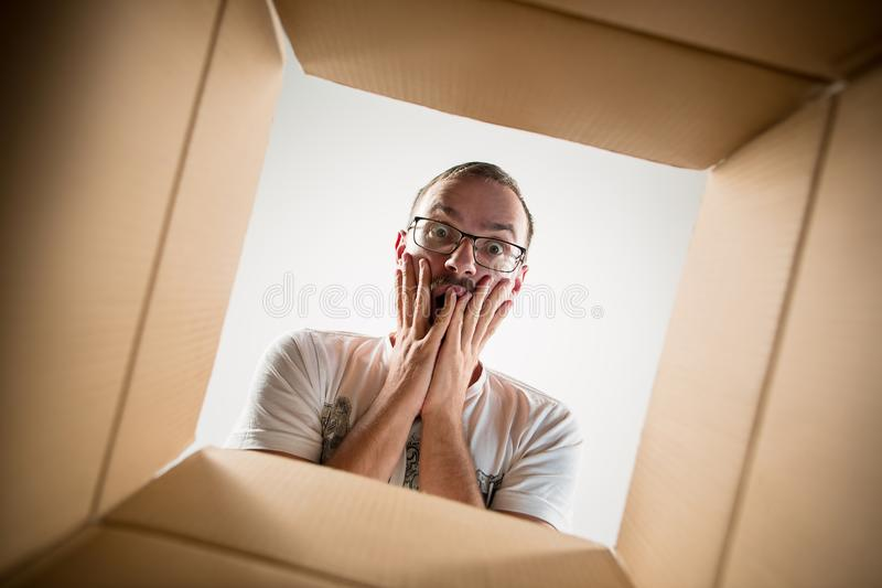 Man unpacking and opening carton box and looking inside. The surprised man unpacking, opening carton box and looking inside. The package, delivery, surprise royalty free stock photos