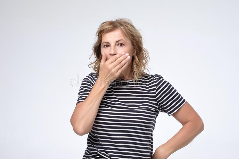 Surprised mature woman covering mouth with hand and staring at camera. Trying to keep secret. I can not believe my eyes concept royalty free stock image