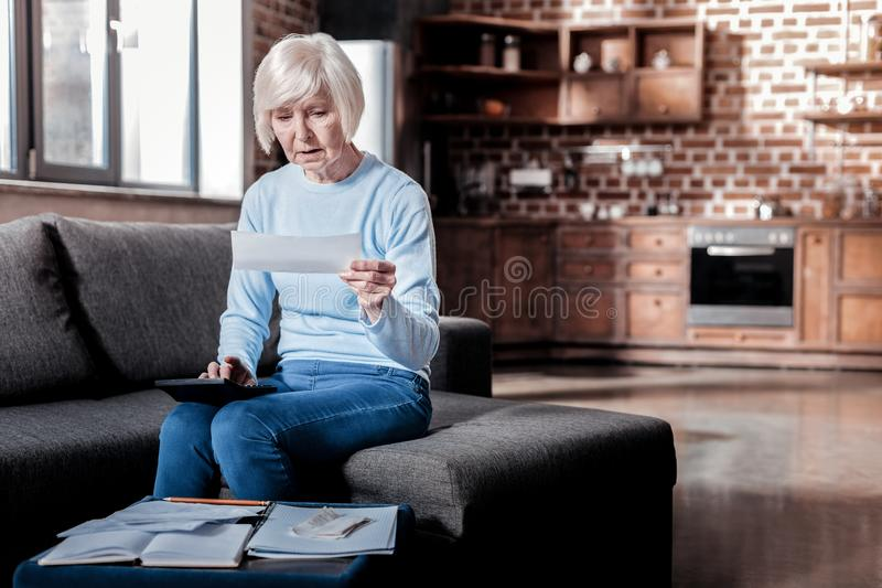Surprised mature woman using calculator royalty free stock images