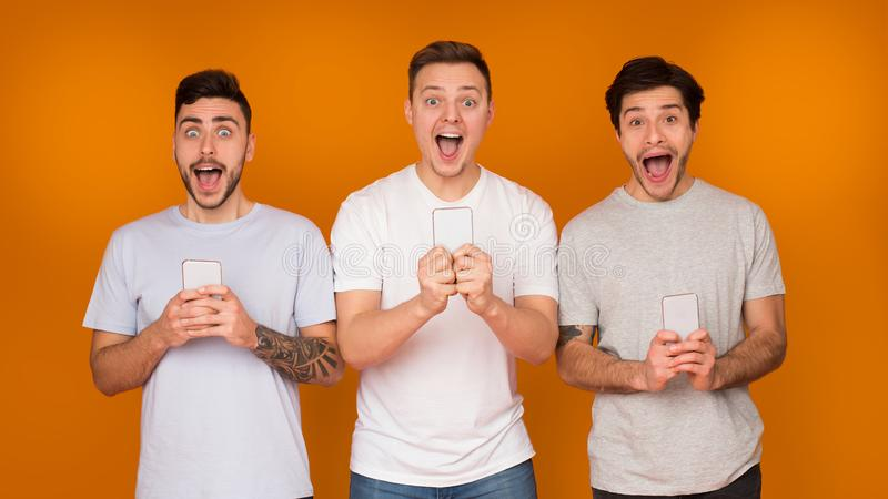 Surprised men holding phones and looking at camera royalty free stock images